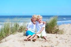 Irmãos gêmeos que jogam na praia imagem de stock royalty free