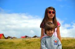 Irmãos: Menino e menina brancos novos com óculos de sol imagens de stock royalty free