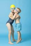 Irmãos novos no roupa de banho que abraçam e que beijam sobre o fundo azul Fotografia de Stock