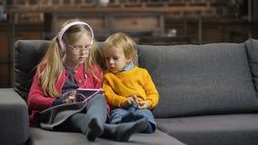 Irmãos pequenos doces que usam o PC da tabuleta no sofá video estoque