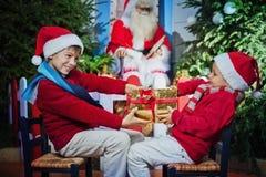 Irmãos que afirmam para o presente do Natal fotos de stock royalty free