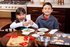 Irmãos que cozem biscoitos do feriado fotos de stock royalty free