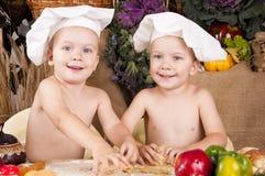 Irmãos que cozinham no cozinheiro chefe \ 'nos chapéus de s Fotografia de Stock Royalty Free