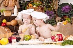 Irmãos que cozinham no cozinheiro chefe \ 'nos chapéus de s Fotografia de Stock