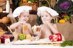 Irmãos que cozinham no cozinheiro chefe \ 'nos chapéus de s Fotos de Stock