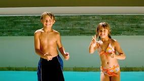 Irmãos que dançam junto na frente da piscina vídeos de arquivo