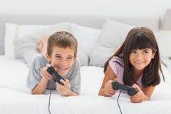 Irmãos que encontram-se na cama que joga jogos de vídeo fotografia de stock royalty free