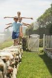 Irmãos que equilibram ao andar em seguido na parede de pedra fotografia de stock