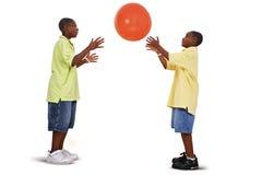 Irmãos que jogam com a esfera alaranjada gigante fotos de stock royalty free