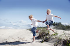 Irmãos que jogam na praia imagem de stock royalty free