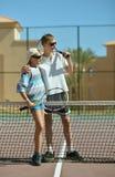 Irmãos que jogam no campo de tênis Fotografia de Stock