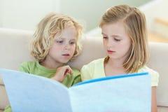 Irmãos que lêem o compartimento no sofá imagem de stock