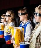 Irmãos que olham o filme 3D no teatro do cinema Imagens de Stock