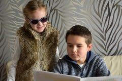 Irmãos que olham um jornal fotos de stock royalty free