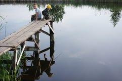 Irmãos que pescam no banco de rio Crianças que situam com as varas nas mãos foto de stock royalty free