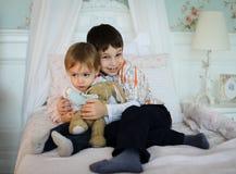 Irmãos que sentam-se em uma cama que guarda-se imagens de stock royalty free