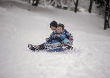 Irmãos que sledging abaixo do monte Fotografia de Stock