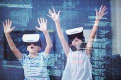 Irmãos que usam auriculares da realidade virtual 3d na sala de visitas Fotografia de Stock Royalty Free