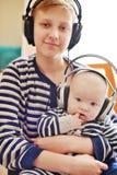 Irmãos que vestem fones de ouvido foto de stock royalty free