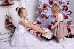 Irmãs adoráveis com o cabelo louro que levanta ao lado da árvore de Natal Imagem de Stock Royalty Free