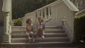 Irmãs afro-americanos adoráveis que sentam-se em escadas vídeos de arquivo