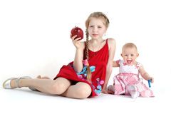 Irmãs 8 anos e bebês de onze meses com maçã Fotografia de Stock Royalty Free