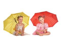 Irmãs bonitas dos gêmeos com os guarda-chuvas isolados fotografia de stock