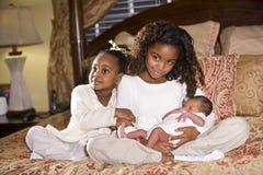 Irmãs com irmão recém-nascido fotografia de stock