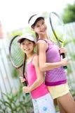 irmãs de volta à parte traseira com uma raquete de tênis cada um Fotografia de Stock Royalty Free