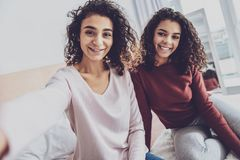 Irmãs deleitadas positivas que sentam-se na cama fotos de stock