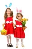 Irmãs felizes com orelhas e ovos da páscoa do coelho Imagem de Stock
