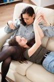 Irmãs felizes e rindo na sala de visitas Fotos de Stock Royalty Free