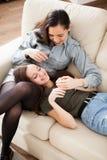 Irmãs felizes e rindo na sala de visitas Imagens de Stock Royalty Free