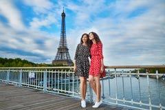 Irmãs gêmeas bonitas na frente da torre Eiffel imagens de stock