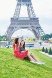Irmãs gêmeas bonitas na frente da torre Eiffel em Paris, França fotografia de stock royalty free