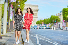Irmãs gêmeas bonitas na frente de Arc de Triomphe Imagem de Stock Royalty Free