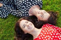 Irmãs gêmeas bonitas que encontram-se na grama fotografia de stock royalty free