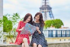Irmãs gêmeas bonitas que usam o mapa na frente da torre Eiffel Foto de Stock Royalty Free