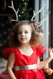 Irmãs gêmeas das meninas em vestidos vermelhos que ficam perto da janela que espera Santa Crianças bonitos com chifres dos cervos fotos de stock