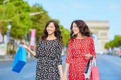 Irmãs gêmeas felizes que fazem a compra em feriados em França Fotos de Stock