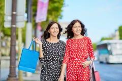 Irmãs gêmeas felizes que fazem a compra em feriados em França Foto de Stock Royalty Free