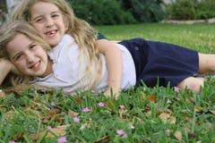 Irmãs gêmeas que colocam na grama Fotografia de Stock
