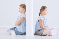 Irmãs gêmeas separadas pela parede fotos de stock