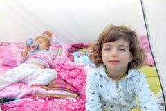 Irmãs internas dois felizes da barraca de acampamento das meninas imagem de stock