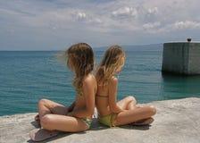 Irmãs irritadas dos gêmeos na baliza no porto marítimo Imagem de Stock
