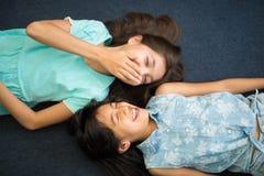 Irmãs mais nova bonitos que riem o encontro no tapete azul Fotos de Stock