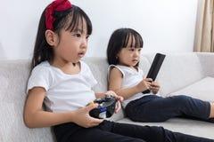Irmãs mais nova chinesas asiáticas que jogam jogos da tevê no sofá fotografia de stock royalty free