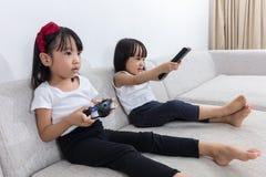 Irmãs mais nova chinesas asiáticas que jogam jogos da tevê no sofá fotos de stock royalty free
