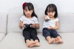 Irmãs mais nova chinesas asiáticas que jogam jogos da tevê no sofá foto de stock royalty free