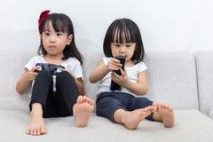 Irmãs mais nova chinesas asiáticas que jogam jogos da tevê no sofá imagem de stock